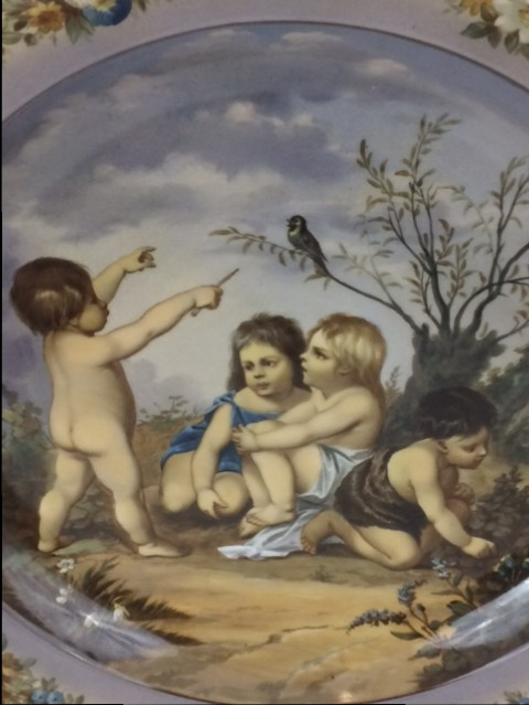 Ausgesprochen aufwendig gestalteter KPM Berlin Porzellan Wandteller in der Anmutung von antiker italienischer Keramik. Mit vier fein gemalten Kindern in einer idyllischen Gartenlandschaft und umlaufend detailliert gemaltem Blumenkranz auf der Tellerfahne.